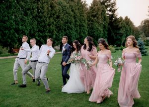 bridesmaids dressed in pink dresses best men and wedding couple are happily walking on the green yard