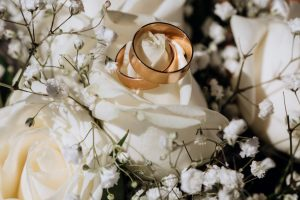 golden wedding rings white rose from wedding bouquet