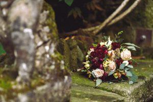 rich red autumn wedding bouquet lies stone footsteps